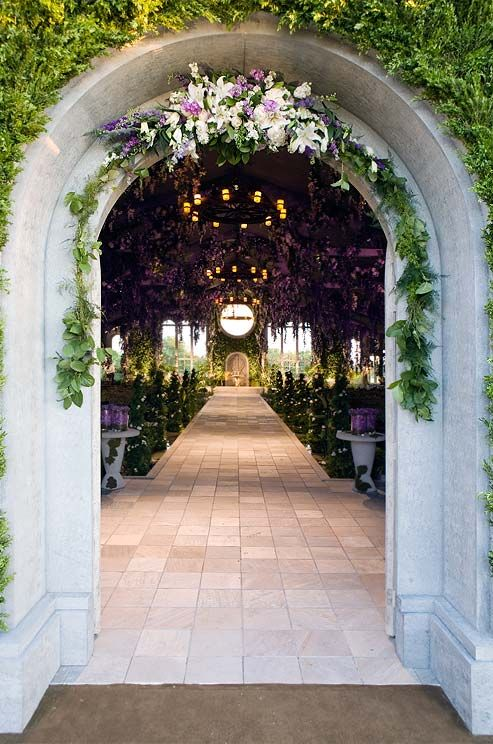 An archway decorated with flowers in shades of purple and white leads to a lush, romantic interior.