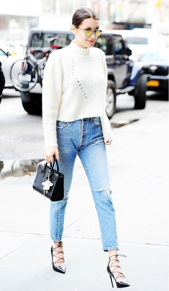 Bella Hadid wears a cropped sweater, distressed jeans, lace-up heels, mirrored sunglasses, and a mini Saint Laurent bag