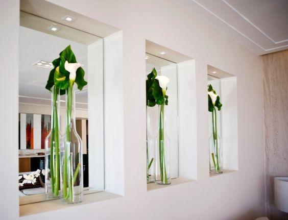 Para os nichos das paredes, a arquiteta Paula Ferraz escolheu garrafas transparentes com folhas da orquídea do gênero Oncidium e flores copo de leite artificiais