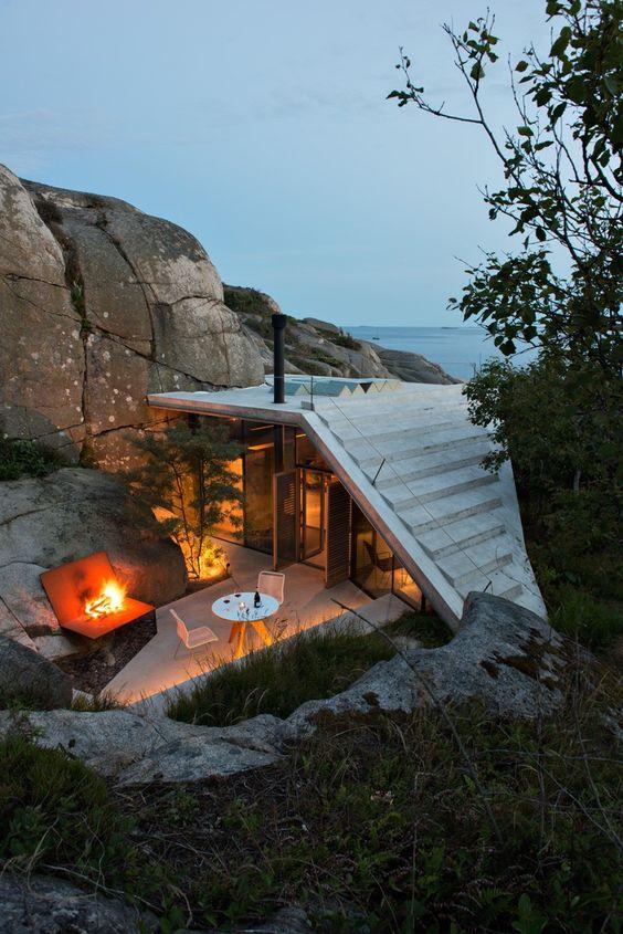 Les architectes norvégiens du studio Lund Hagem ont conçu ce petit coin de paradis niché à flanc de falaise, à l'abri du vent et des regards mais avec une belle vue sur la mer, au sud-est du pays, à Sandefjord.  Il faut suivre un sentier pour accéder à cette petite habitation de 30 m2 dont la forme du toit en béton épouse les rochers alentours. À l'arrière de la cabine, on retrouve un espace extérieur avec table, chaises et un coin feu. À l'intérieur, des murs de verre offrent une vue sur...