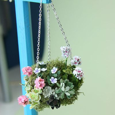 A dolls house scale planted moss hanging basket hung from a chain on a lampstand.