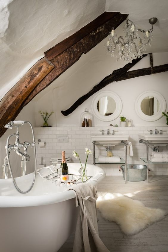 Unique home stays beautiful bathroom in modern country style with wood beams and bare claw tub