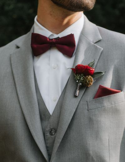 Burgundy boutonniere for groom with ranunculus. Visions of warm Autumn colors, fun pumpkin accents and rich details filled this fall wedding in Tennessee. The designs featured some breathtaking seasonal, fluffy blooms. The color palette featured vivid burgundy coupled with gray, peach and burnt orange. This modern twist on traditional Fall colors perfectly complemented the cozy atmosphere at Loveless Barn. #weddings #fallwedding #florals #weddingflowers #groom #boutonniere #floraldesigner
