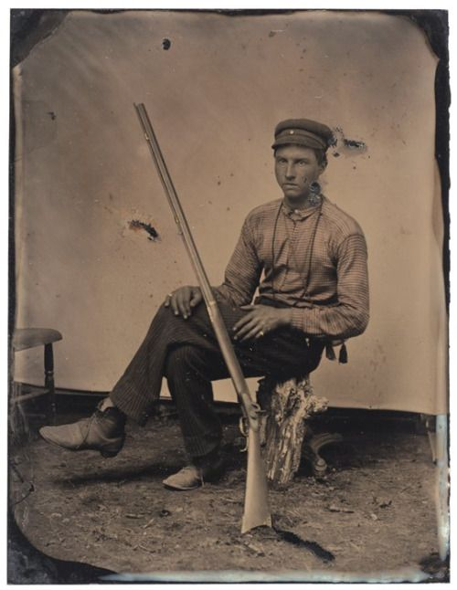 ca. 1860-70's, [tintype portrait of a man with a rifle seated on a tree stump] via the San Francisco Museum of Modern Art, Photography Collection