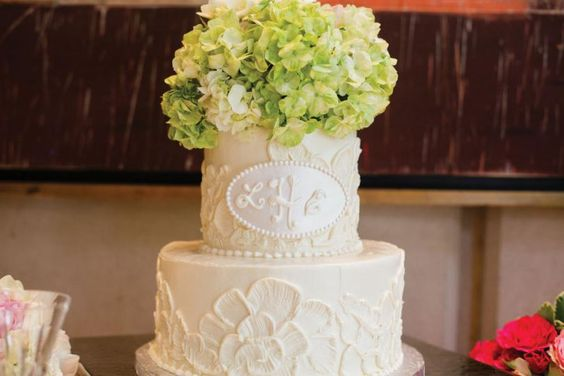 Gorgeous white cake with patterns, monogram, and green flower topper