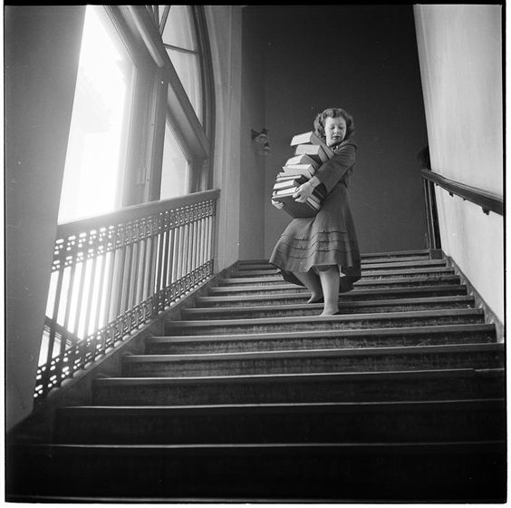 Stanley Kubrick, Woman carrying a large stack of books down stairs, Columbia University, 1948