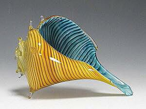 """Adam Kaser Hand blown Whelk Shell in Carmel Blue - Green.  """"Beginning with a bubble, Adam pulls the points of the shell by hand, giving each their unique quality"""". Available in three sizes.  Small 3"""", medium 4-6"""",  large 7-10"""".  All sizes are approximate and vary."""