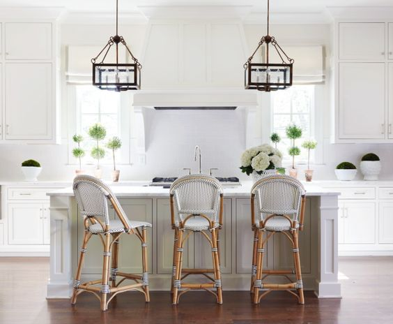 Classic white kitchen with Parisian bistro bar stools, lanterns, and potted topiary. Sarah Bartholomew Traditional Colorful Decor.
