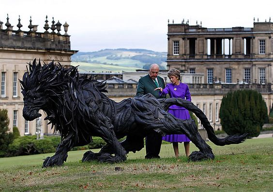 The Duke and Duchess of Devonshire view the sculpture Lion 2 by Ji Yong-Ho in the gardens of their home Chatsworth House