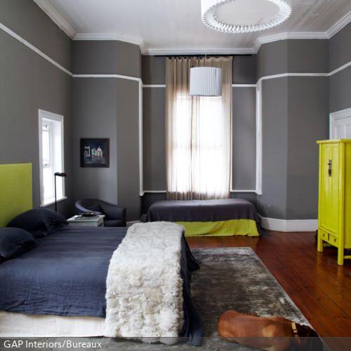 Der graue Orientteppich im Shabby Chic ist das perfekte Accessoire für ein Schlafzimmer, in dem auch ein treuer Vierbeiner ruht. Er wirkt nicht so schnell schmutzig und bietet eine große Fläche zum Ausbreiten. Die Tapete in Grau fügt sich farblich passend ein. Betthaupt, Decke auf der Gästeliege und Schrank in Neongelb setzen aufregende Akzente.