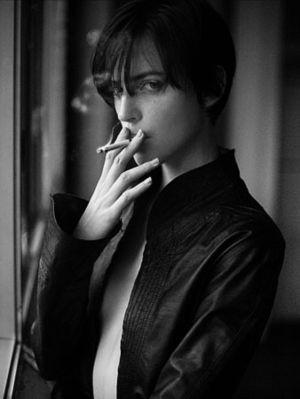 ショートヘアの女性がタバコを吸う画像