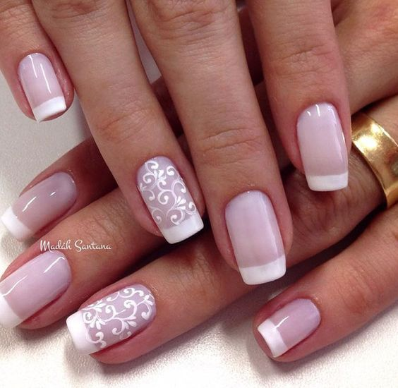 Lace designed white French tips. Beautiful and artistically looking French tips with lace designs in white nail polish on the bottom part of the nails.: