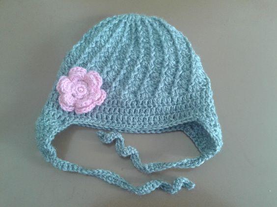 Touca para deixar sua bebê bem quentinha. <br>Feita em crochê com lã antialérgica para bebê, tem uma flor <br>do lado bordada com uma pérola no centro e cobre as orelhas. <br>Tamanhos (circunferência): <br>Rn - 36 - 38 cm <br>1-3 meses (38-40 cm) <br>3-6 meses (42-44 cm) <br>Faço na cor que você quiser. <br>Por favor coloque o tamanho e a cor na hora da compra.