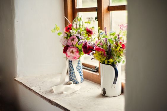 Pretty pale pink and red flowers in vintage jugs.  Photos by http://www.agatomaszek.com/