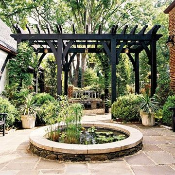 The dark color of this pergola emphasizes   its linear structure ... and contrasts nicely with the round white   concrete-topped stone water garden.