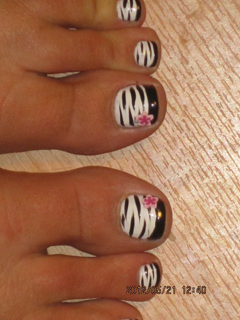 Pretty pedicure: White Polish zebra print with Black French tips and a Pink flower Decal.