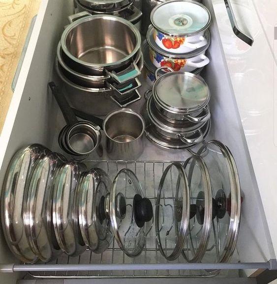 Panelas e tampas organizadas no armário da cozinha