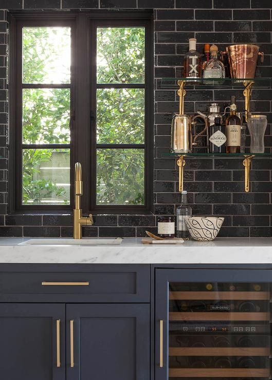 Gorgeous Wet Bar Features Dark Blue Shaker Cabinets Adorned With Brushed Brass Hardware Paired White Marble Countertops And A Glossy Black Til