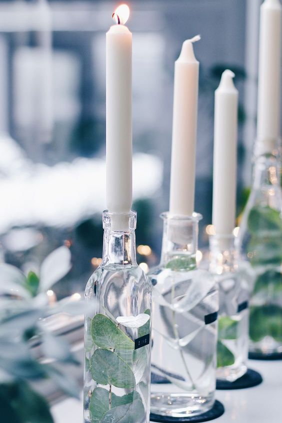 So pretty. Scandi-style. Candles in bottles with greenery.