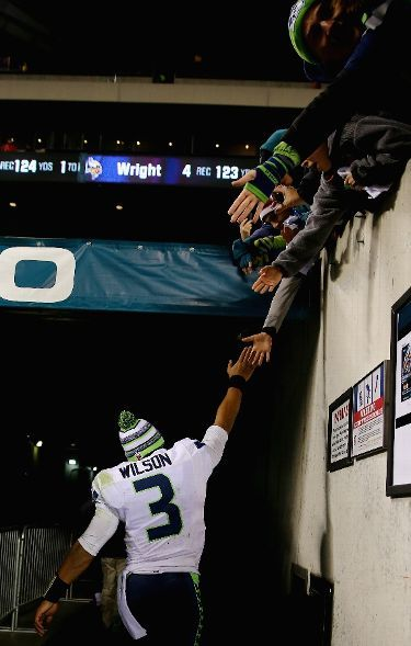 PHILADELPHIA, PA - DECEMBER 07: Quarterback Russell Wilson #3 of the Seattle Seahawks shakes hands with patrons as he leaves the field after their 24-14 win over the Philadelphia Eagles at Lincoln Financial Field on December 7, 2014 in Philadelphia, Pennsylvania. (Photo by Elsa/Getty Images) Seattle Seahawks vs. Philadelphia Eagles - Photos - December 07, 2014 - ESPN