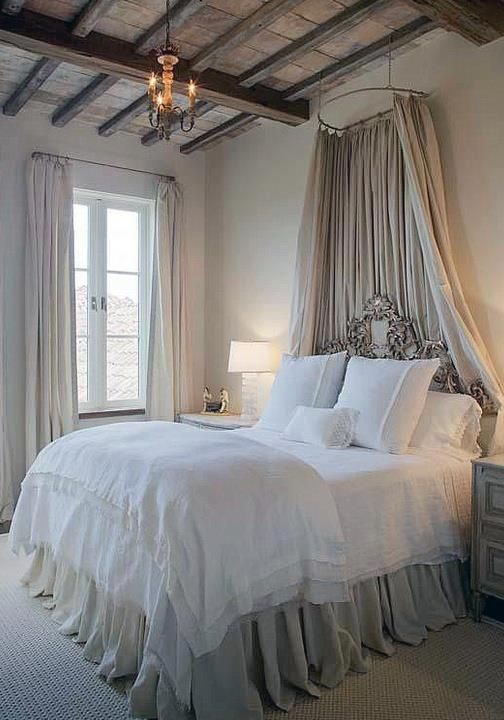 elegantly dressed bed...maybe a bit elaborate ...and maybe a bit too high...but looks good in this setting