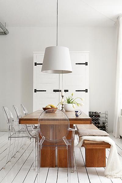lucite chairs, wood table, white door with black hinges door as art