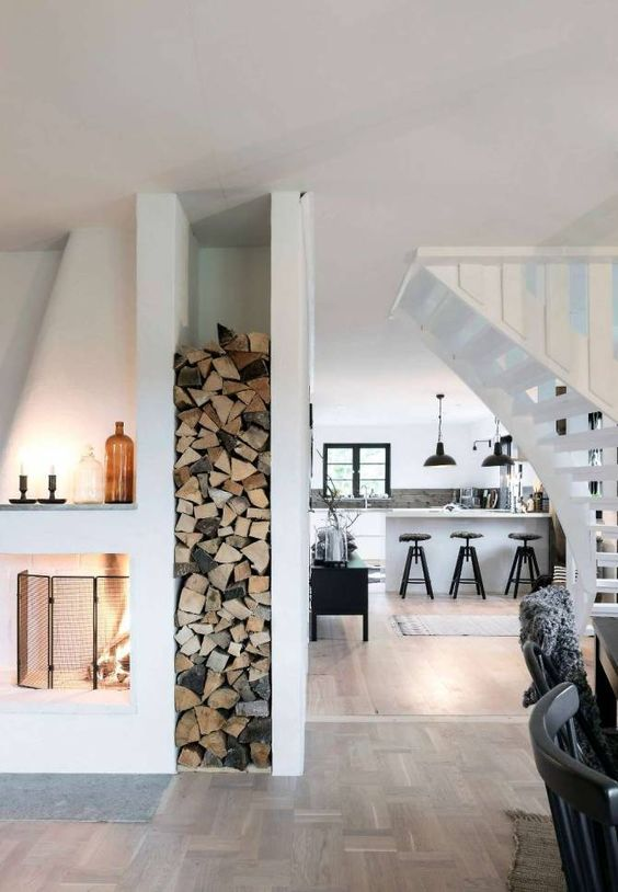 Cabin interior inspiration. white and wood. wood storage next to fireplace.: