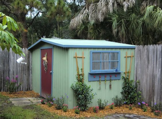 Started as a basic white metal shed, she painted it, added trim, a window painted with Krylon Looking Glass Mirror-Like Paint, and a trellis for climbing plants: