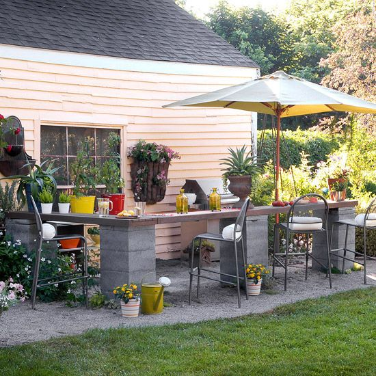 Sure, outdoor bars can be as ornate as you'd like -- but they also work equally well in a DIY, easygoing setup. This one has all the necessary elements -- seating, storage, serving -- as well as colorful extras with container plants, wall hangings, and an umbrella. But the materials -- a wood counter and concrete blocks -- and setup come together in just an afternoon./: