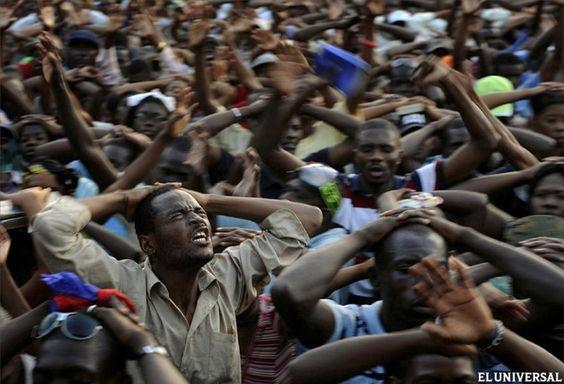 """Año 2010. Supervivientes del terremoto rezan en los Campos de Marte en Puerto Príncipe. La foto es parte de una serie de tomas sobre la catástrofe ocurrida en Haití por un terremoto en 2010. Fueron tomadas por Carol Guzy, Nikki Kahn y Ricky Carioti, de The Washington Post. Los profesionales recibieron el premio Pulitzer en la categoría """"Fotografía de Última Hora""""."""