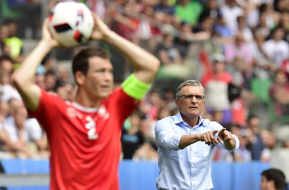 Poland's coach Adam Nawalka (R) speaks with his players as Switzerland's defender Stephan Lichtsteiner brings the ball into play during the Euro 2016 round of sixteen football match Switzerland vs Poland, on June 25, 2016 at the Geoffroy Guichard stadium in Saint-Etienne. / AFP / TOBIAS SCHWARZ