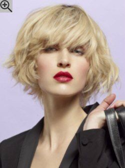 Blonde chin length bob with a thick fringe. With texturing, light layers and undone styling.