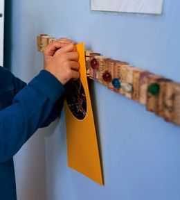 Corks glued to a yard stick = bulletin board. So smart!