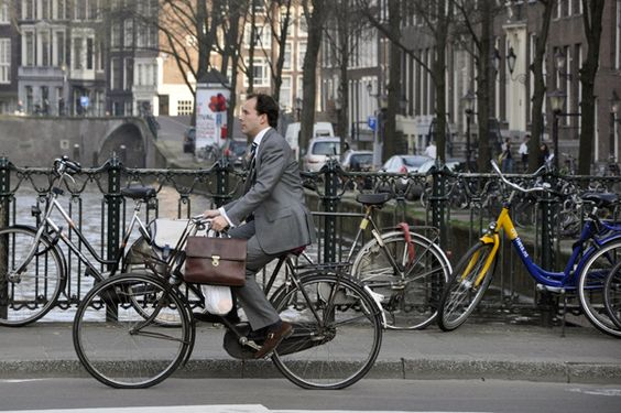 Crazy loving how commuting is done by bike in the Netherlands. Very chic, briefcase and all.