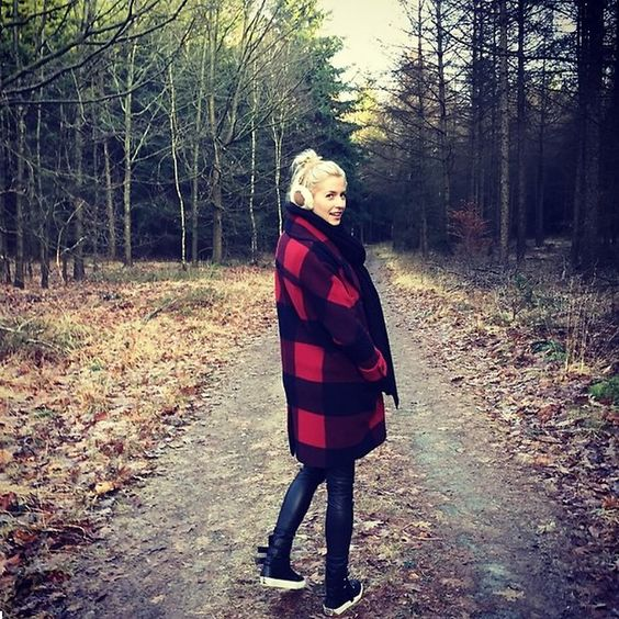 Fashion-Looks: Lena steht im Walde und sieht toll aus! Der Mantel mit den großen Karos ist von Tommy Hilfiger. Dazu trägt sie Sneakers und gegen die Kälte, süße Ohrenschützer.