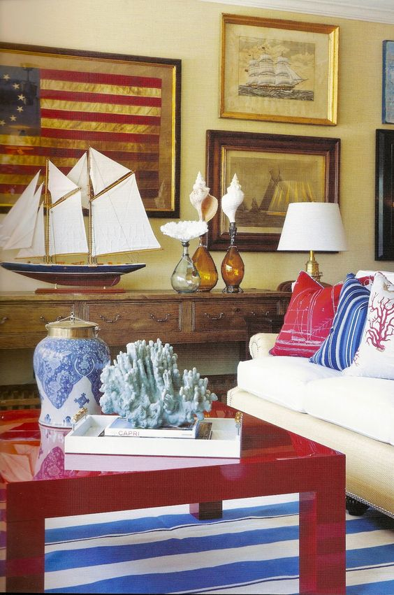 Barclay Butera's red, white, and blue Americana living room. American flag framed on wall, red laquer table, and bright cheery blue accents. #traditionaldecor #redwhiteblue #americanflag #livingroom #casual #coastal