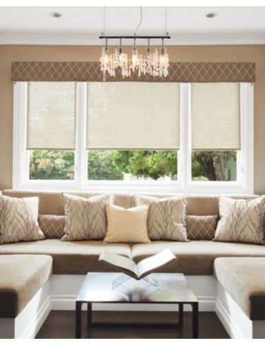 """Classic Roller Shades in 14052 Island Stripe/ Taupe Layered with Tailored Upholstered Cornice in 14468 Opulant Ogee/ Mocha. 18"""" Tailored Square Pillow in 14577 Silk Dupioni/ Champagne 14577,  22"""" Tailored Square Pillow in 14490 Brances/ Taupe and a Boudoir Pillow in 14468 Opulant Ogee/ Mocha"""