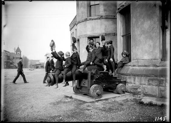 Boys on a gun  VPL Accession Number: 6871  Date: 1907  Photographer/Studio: Timms, Philip  Content: Boys sitting and waving on a naval gun outside the Beatty Street Drill Hall as members of the Duke of Connaught's Own Rifles enter in the background