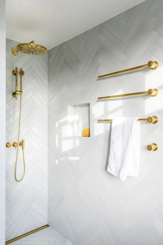 Small luxury bathroom white tiles and gold interior.