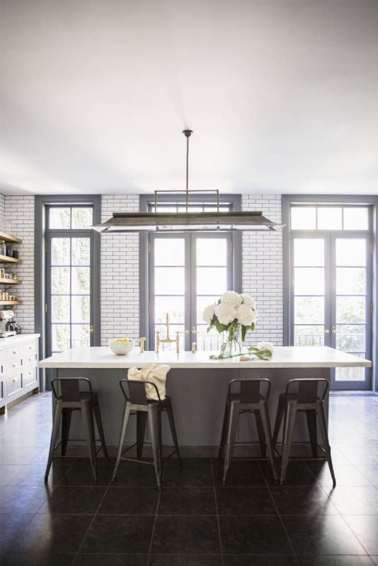 Large windows and doors in kitchen. Love this huge island and light fixture.: