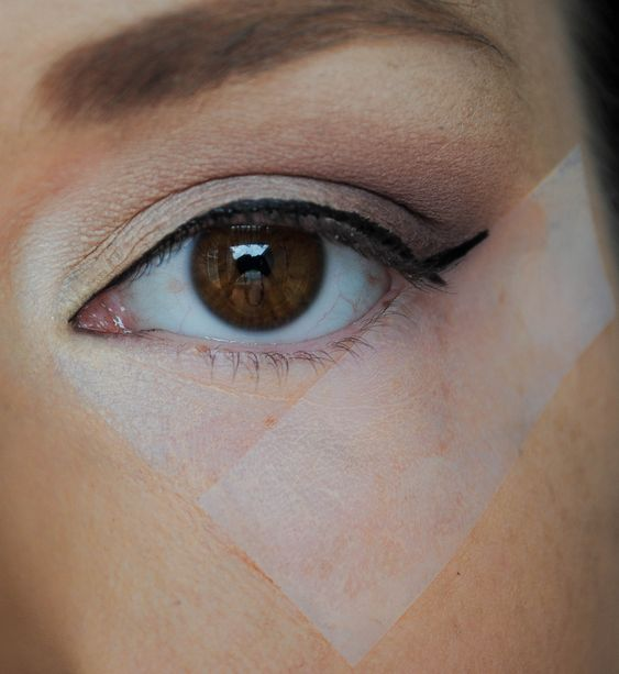 This is a long time makeup artist trick.  using tape or a credit card to make the perfect winged liner: