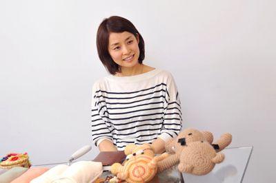 ぬいぐるみの前に座っている石田ゆり子