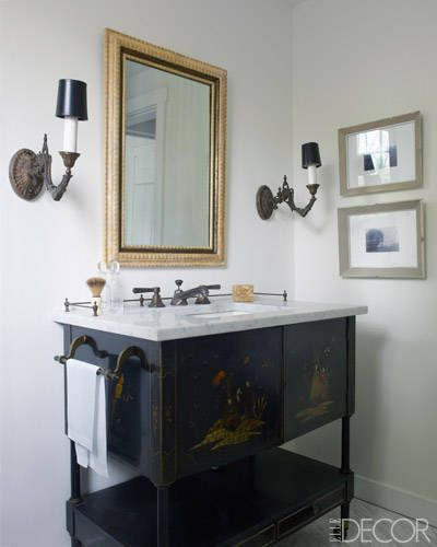 With a Light Touch Electrified gas sconces in a guest bath flank a vanity that was updated with a Carrara marble top; the sink is by Kohler, and the photographs were taken by Morey as a child.