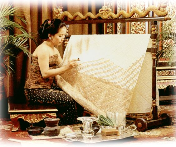 A Batik Tulis maker applying melted wax following the pattern using canting.