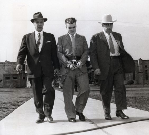 Charles Starkweather, 19, admitted mass-slayer, is flanked by sheriff Merle Karnopp (left) and chief deputy Les Hasson (right) as he is led from place of confinement to the courtroom, 1958. [Getty Images]