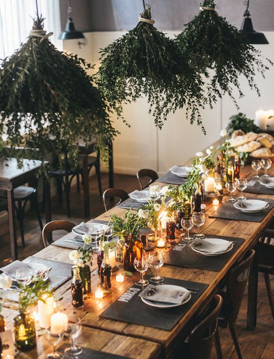 rustic tablescape with greenery-covered lighting fixtures and candlelight - simple but elegant for a wedding reception