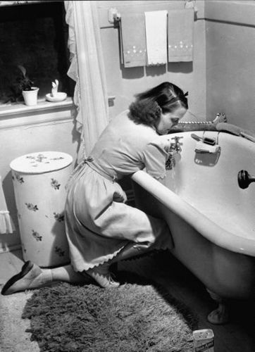 In a familiar scene that all of us can likely relate to, a 1940s woman (in a cute dress, I should point out - note the scalloped hem and sleeves) tackles the task of scrubbing the family bathtub yet again. #vintage #1940s #homemaker #housewife #cleaning: