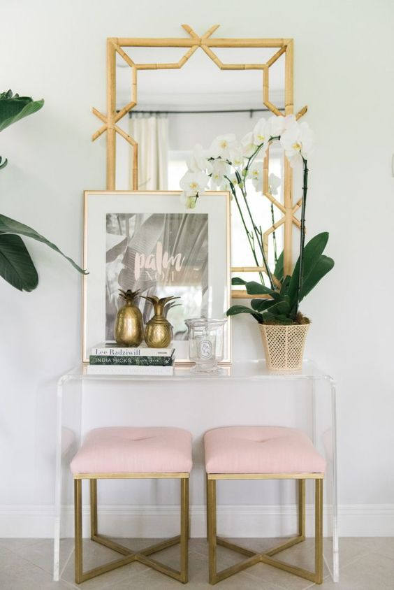 Brass mirror, lucite console and pale pink stools.