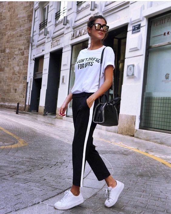 Retrospectiva fashion: 8 tendências que bombaram em 2017. T-shirt branca, calça esportiva preta com listras  branca na lateral, tênis branco