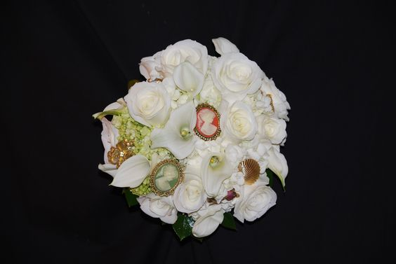 Vintage nosegay of white roses, white mini callas and heirloom cameos and brooches.